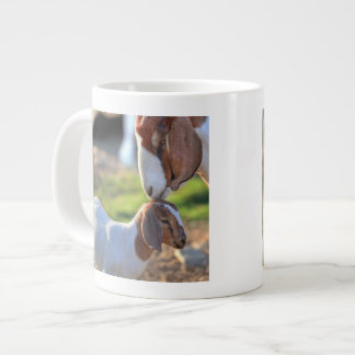 Mother goat kissing her baby on head. large coffee mug