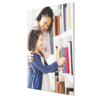 Mother helping daughter choose book on shelf canvas print