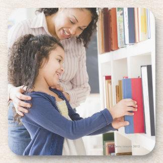 Mother helping daughter choose book on shelf drink coaster