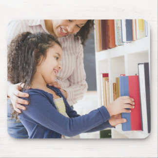 Mother helping daughter choose book on shelf mouse pad