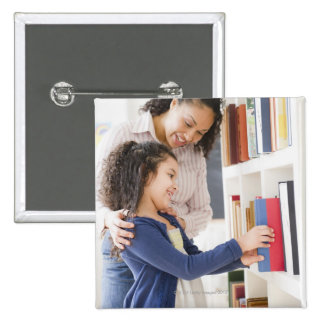 Mother helping daughter choose book on shelf pinback button