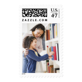 Mother helping daughter choose book on shelf postage