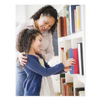 Mother helping daughter choose book on shelf postcard