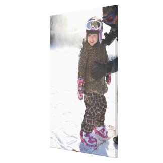 Mother Teaching Daughter To Snowboard Canvas Print