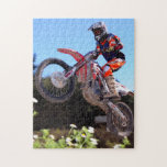"Motocross rider taking the jump jigsaw puzzle<br><div class=""desc"">A motocross rider takes a jump on a dirt track.</div>"