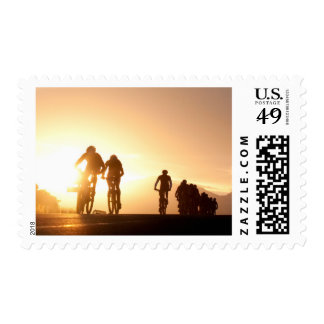 Mountain Bike Riders Make Their Way Over The Top Stamp