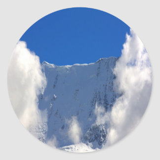 Mountain top flanked by clouds classic round sticker