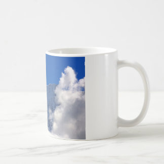 Mountain top flanked by clouds coffee mug