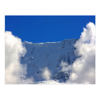 Mountain top flanked by clouds postcard