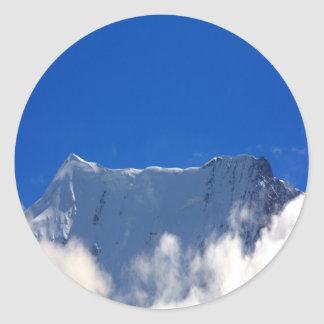 Mountain top over clouds classic round sticker