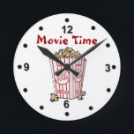 """Movie Popcorn Wall Clock<br><div class=""""desc"""">Fun movie room clock done with a white background and black numbers.  Cartoon graphics of a box of movie popcorn,  in the middle,  and red text reading Movie Time.  Personalize the text to change it.  Makes a great gift idea.</div>"""