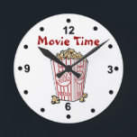 "Movie Popcorn Wall Clock<br><div class=""desc"">Fun movie room clock done with a white background and black numbers.  Cartoon graphics of a box of movie popcorn,  in the middle,  and red text reading Movie Time.  Personalize the text to change it.  Makes a great gift idea.</div>"