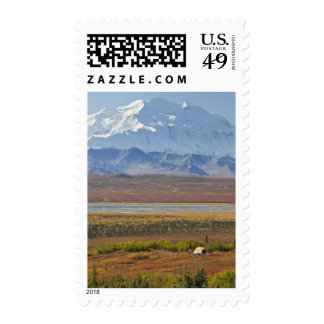 Mt. McKinley towers behind a camper and his tent 2 Stamps