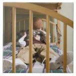 Muchacho (11-13) que miente en la cama, jugando co teja  ceramica