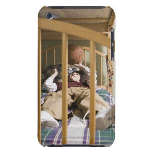 Muchacho (11-13) que miente en la cama, jugando co Case-Mate iPod touch funda