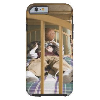 Muchacho (11-13) que miente en la cama, jugando funda resistente iPhone 6