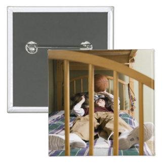 Muchacho (11-13) que miente en la cama, jugando pin cuadrado