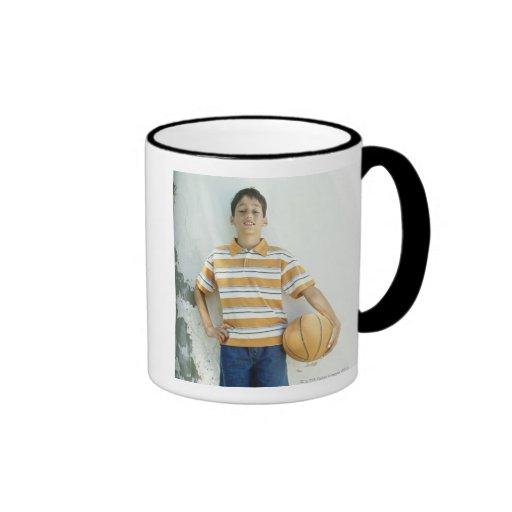 Muchacho (12-13) que se coloca delante de blanco taza de café