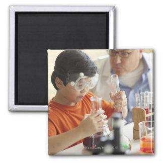 Muchacho (6-7) y profesor en clase de química imán cuadrado