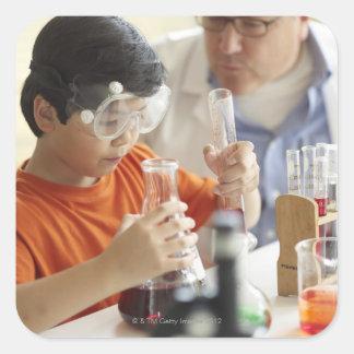 Muchacho (6-7) y profesor en clase de química colcomanias cuadradas