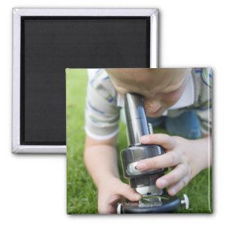 Muchacho (8-9) usando el microscopio ligero, imán cuadrado