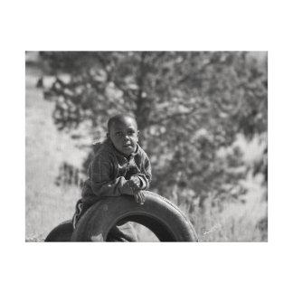 Muchacho africano con el neumático lona envuelta para galerias