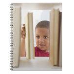 Muchacho afroamericano que selecciona el libro libretas espirales
