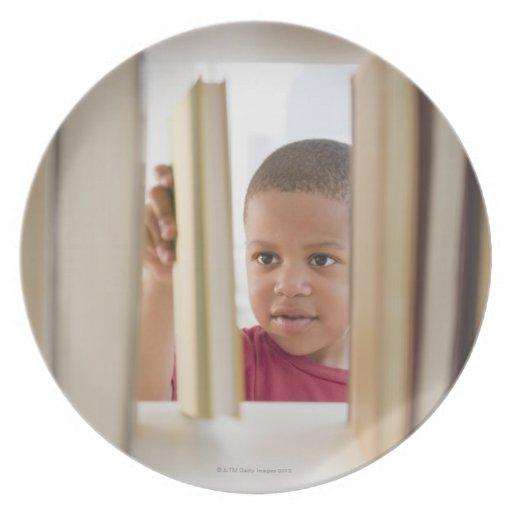 Muchacho afroamericano que selecciona el libro platos de comidas