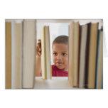 Muchacho afroamericano que selecciona el libro tarjetas
