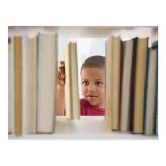 Muchacho afroamericano que selecciona el libro tarjetas postales