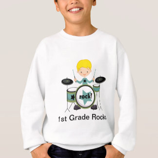 Muchacho cabelludo rubio en rocas de los tambores sudadera
