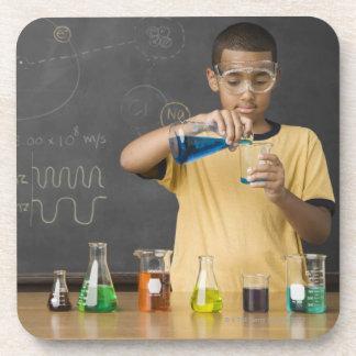 Muchacho de la raza mixta en clase de la ciencia posavasos de bebidas