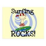 Muchacho de las rocas que practica surf en camiset postal