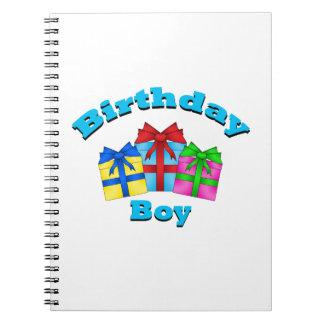 Muchacho del cumpleaños con los presentes libro de apuntes con espiral