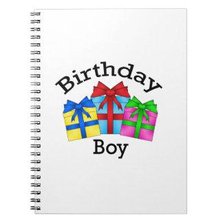 Muchacho del cumpleaños en negro con los presentes libro de apuntes