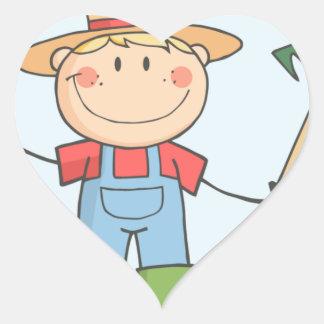 Muchacho del granjero con un rastrillo en hierba colcomanias de corazon