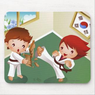Muchacho del karate que se sostiene de madera con tapete de raton