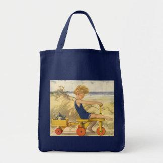 Muchacho del vintage que juega en la playa con los bolsa tela para la compra