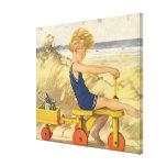 Muchacho del vintage que juega en la playa con los lona estirada galerías