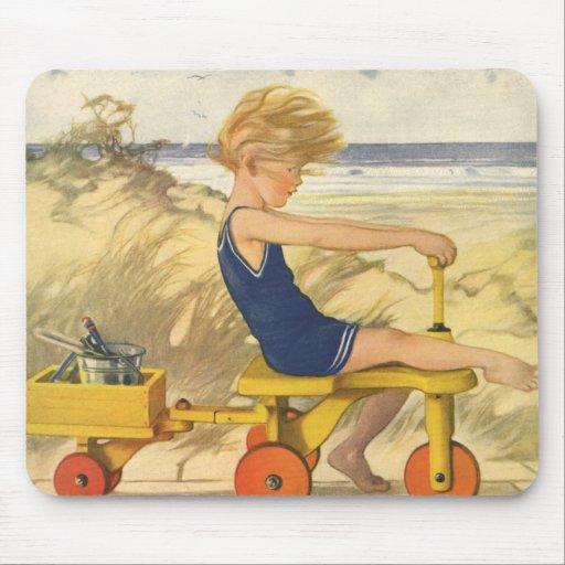 Muchacho del vintage que juega en la playa con los alfombrillas de ratón