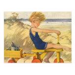 Muchacho del vintage que juega en la playa con los tarjetas postales