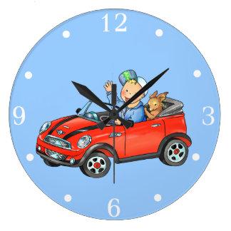 Muchacho en el coche rojo del juguete - reloj de p