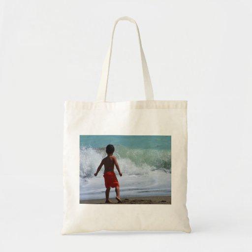 muchacho en la playa que juega en agua bolsa de mano