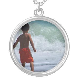 muchacho en la playa que juega en agua colgante redondo