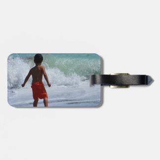 muchacho en la playa que juega en agua etiquetas bolsas