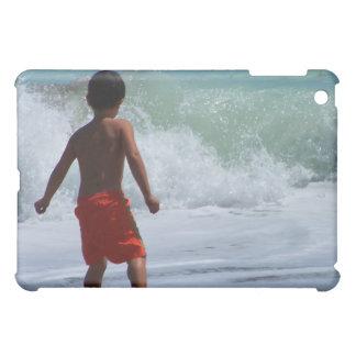 muchacho en la playa que juega en agua