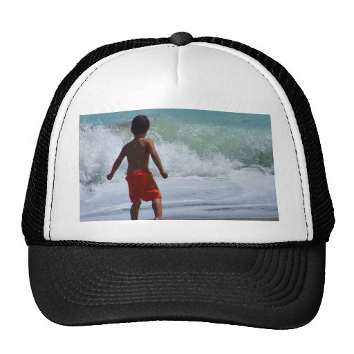 muchacho en la playa que juega en agua gorro