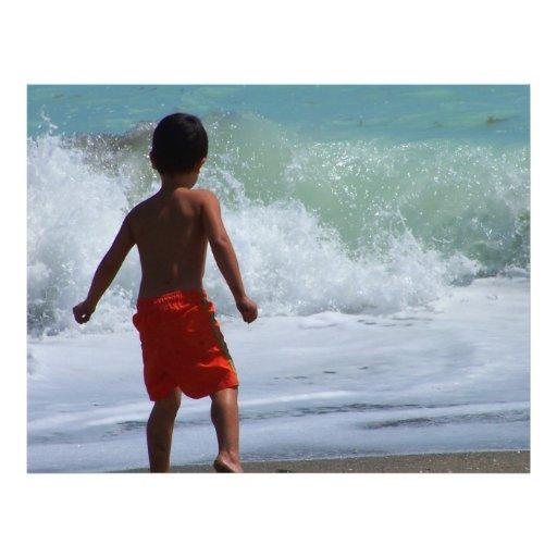 muchacho en la playa que juega en agua membrete