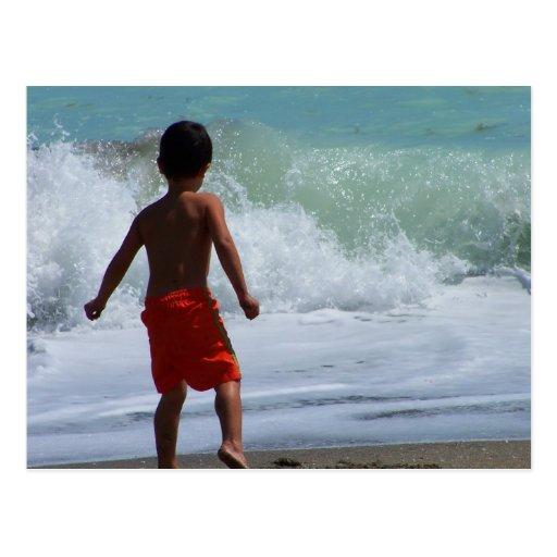 muchacho en la playa que juega en agua postal