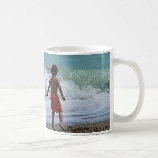 muchacho en la playa que juega en agua taza básica blanca